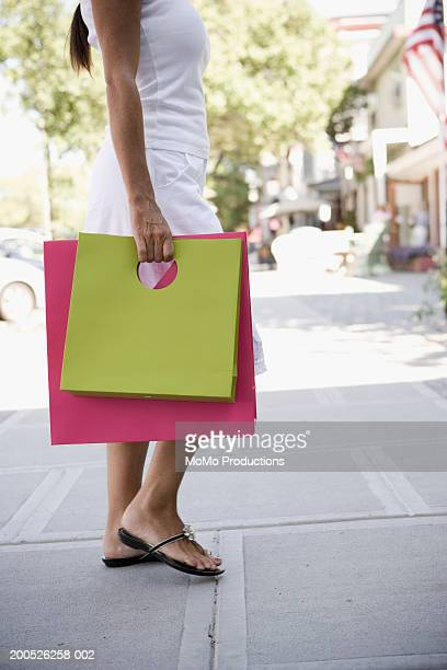 Woman carrying shopping bags, side view, mid section