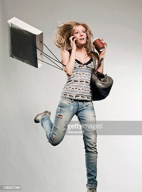 Woman carrying shopping bags, using mobile phone