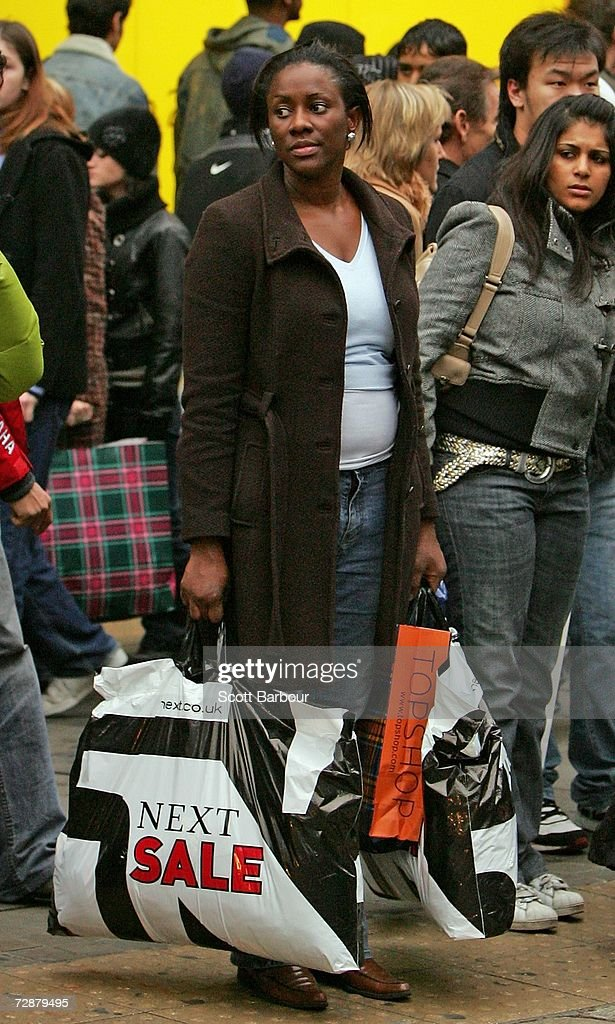 A woman carrying shopping bags waits to cross the road as shoppers rush past her on December 27, 2006 in London, England. With many shops trading for the first time since Christmas Eve, bargain hunters are searching for the best buys as the post-Christmas sales get under way.