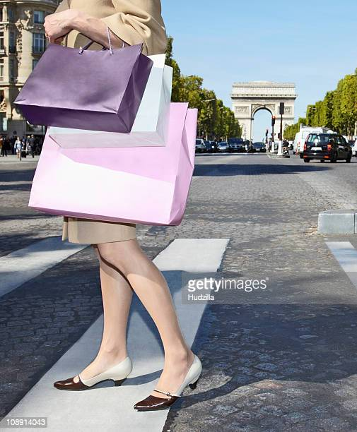 a woman carrying shopping bags walking across a zebra crossing, paris, france - champs elysees quarter stock pictures, royalty-free photos & images