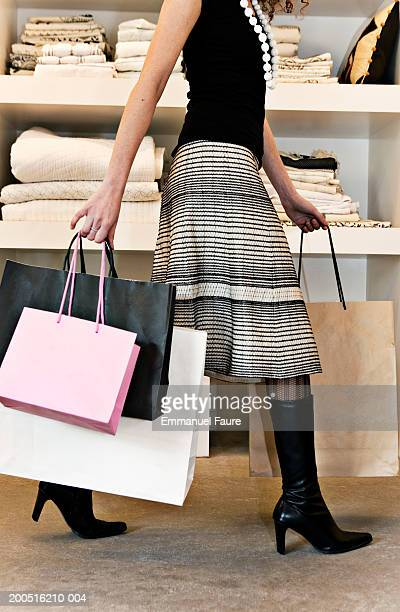 Woman carrying shopping in home ware store, side view, low section