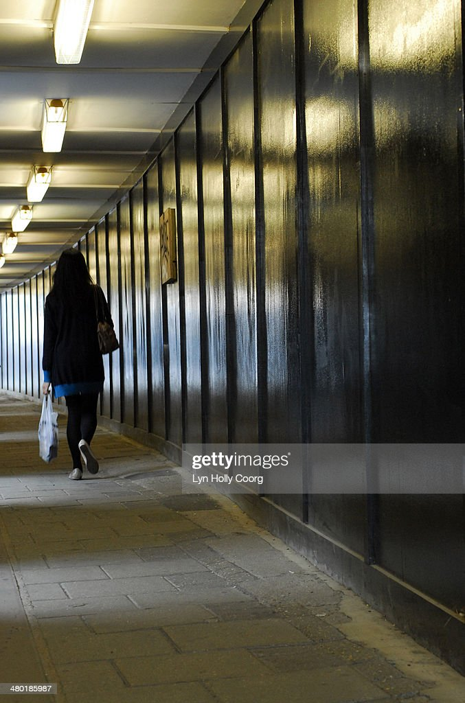Woman carrying shopping walking through underpass : Stock Photo