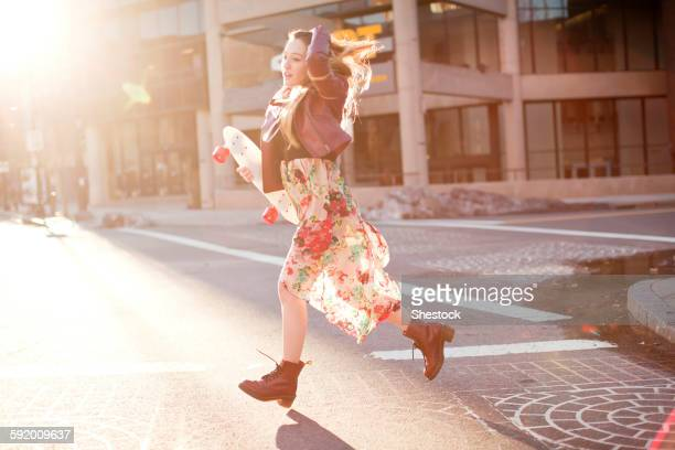 Woman carrying skateboard in city intersection