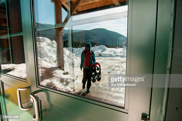 woman carrying snowshoes into the highland center located in crawford notch, nh. - crawford notch stock pictures, royalty-free photos & images