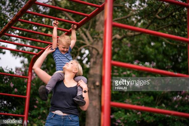 woman carrying son on shoulders below monkey bars - colorectal cancer stock photos and pictures