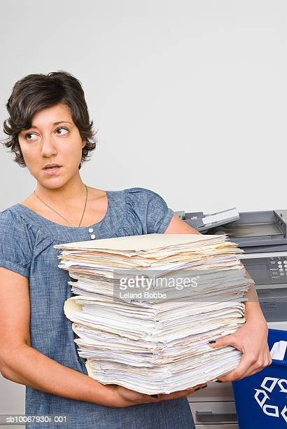 Woman carrying stack of papers at copy machine, looking away