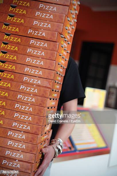 Woman Carrying Stack Of Pizza Boxes