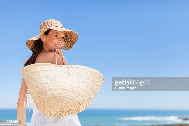 woman carrying straw bag outdoors - one mature woman only stock pictures, royalty-free photos & images