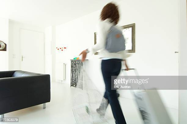 Woman carrying suitcase and birdcage in a living-room