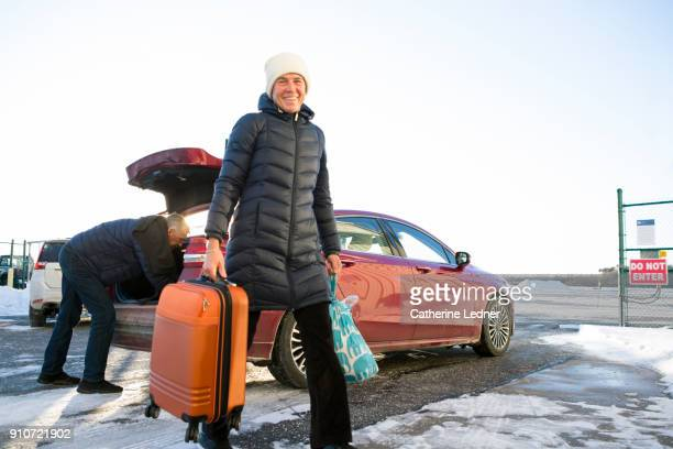 Woman carrying suitcase walking from car in snow