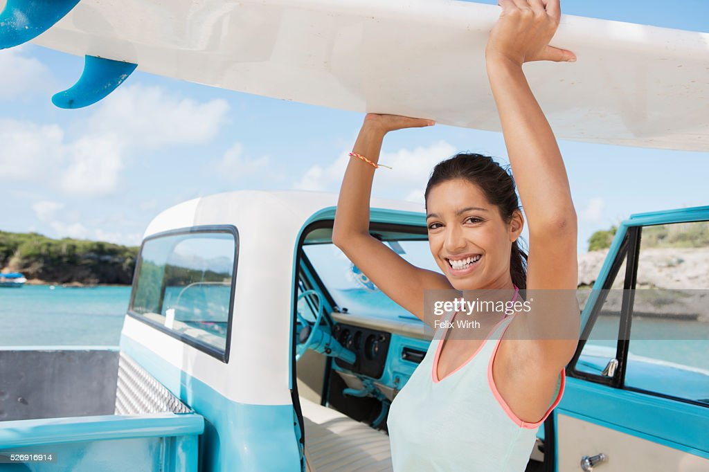 Woman carrying surfboard : Stock Photo
