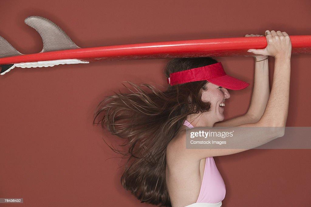 Woman carrying surfboard : Stockfoto