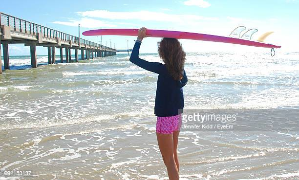 woman carrying surfboard while standing on shore - jennifer kidd stock pictures, royalty-free photos & images