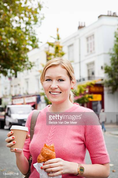 Woman carrying take away coffee with croissant.