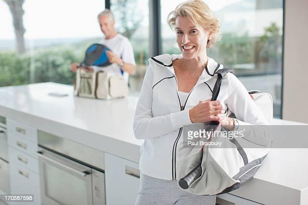 Woman carrying tennis racquet in gym bag