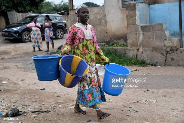 Woman carrying three large buckets arrives to receive water distributed by workers of the National Office of Drinking Water to the population on June...