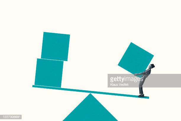 woman carrying turquoise block on weight scale - バイアス ストックフォトと画像