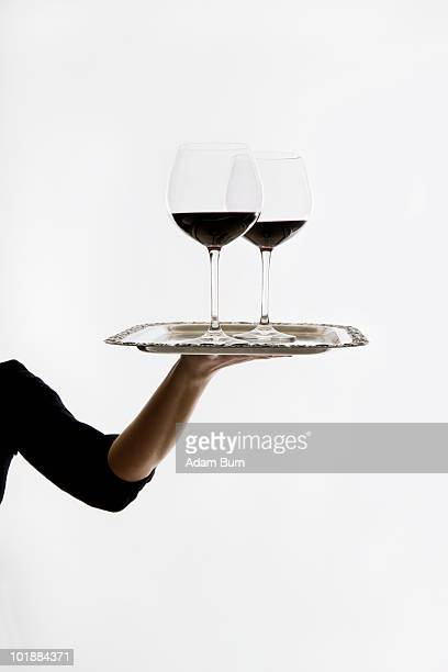 A woman carrying two of glasses of red wine on a tray