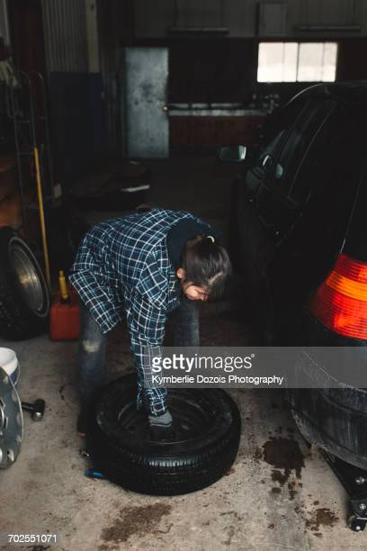 woman carrying tyre in workshop - older woman bending over stock pictures, royalty-free photos & images