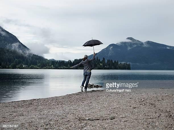Woman carrying umbrella by still lake