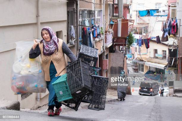 Woman carrying used plastic containers in Tarlabasi beighbourhood, Istanbul Turkey