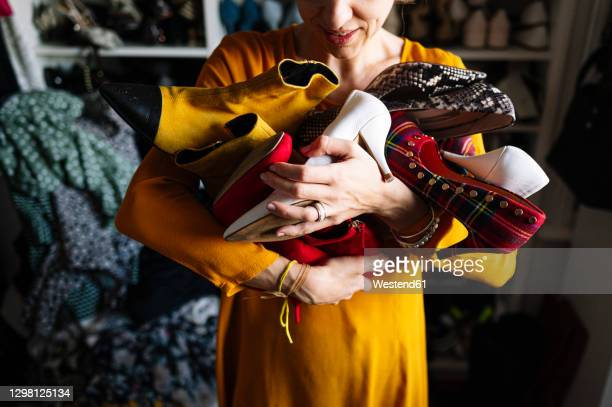 woman carrying variation of shoes in wardrobe at home - grand groupe d'objets photos et images de collection
