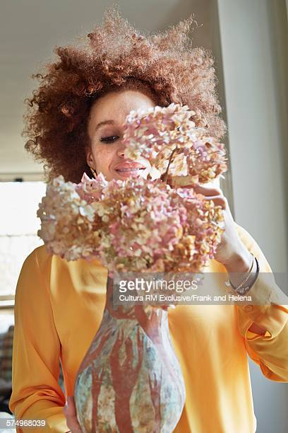 Woman carrying vase of flowers