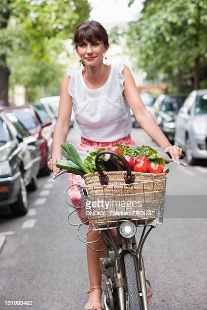 Woman carrying vegetables on a bicycle, Paris, Ile-de-France, France