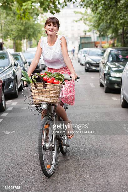 woman carrying vegetables on a bicycle, paris, ile-de-france, france - ile de france fotografías e imágenes de stock