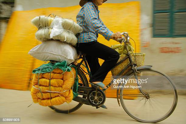 Woman carrying vermicelli on bicycle