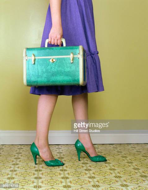 Woman carrying vintage suitcase