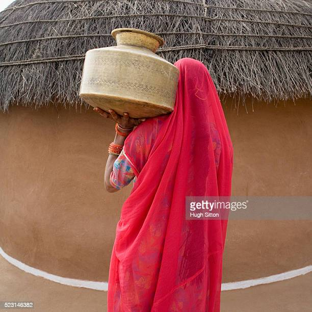 woman carrying water jug - hugh sitton stock pictures, royalty-free photos & images