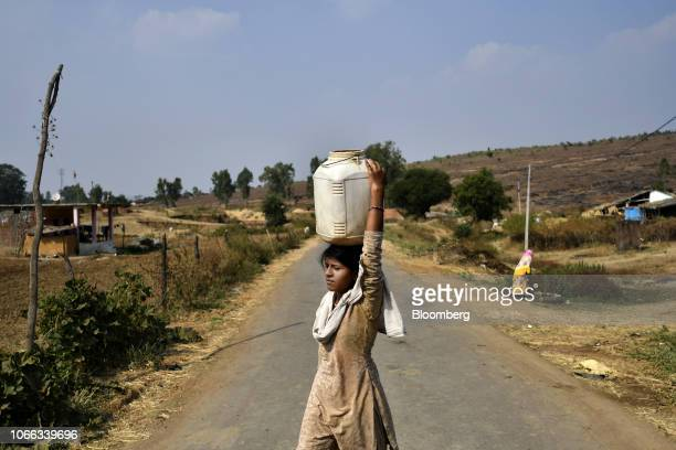 A woman carrying water on her head crosses a road in Bhopal District Madhya Pradesh India on Tuesday Nov 20 2018 Key Indian states are voting in...