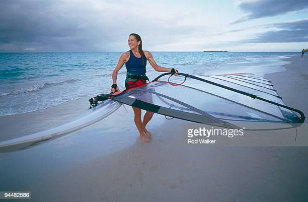 Woman carrying wind surfboard from ocean
