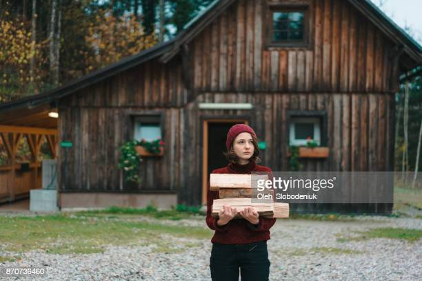 Woman carrying  wood  to the house
