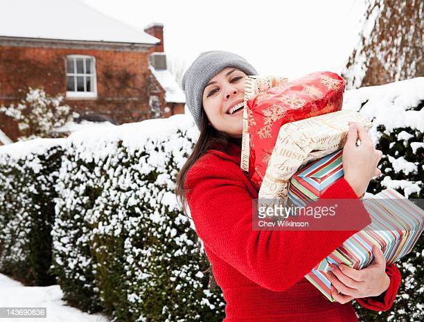 Woman carrying wrapped gifts in snow