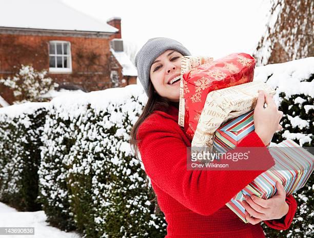 Femme transportant des cadeaux dans la neige