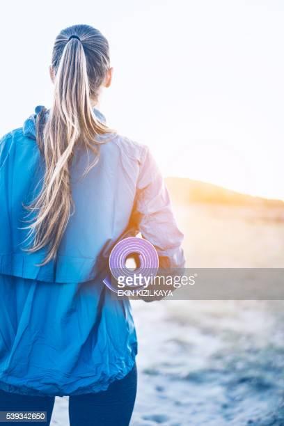 Woman carrying yoga mat