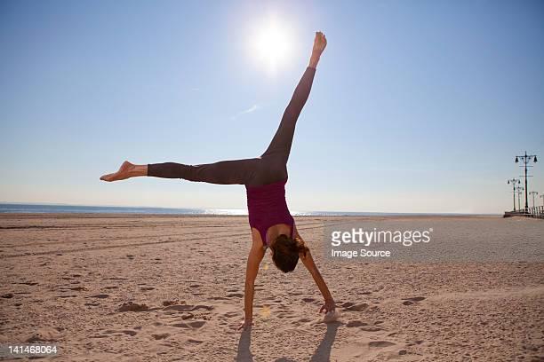 Woman cartwheeling on beach