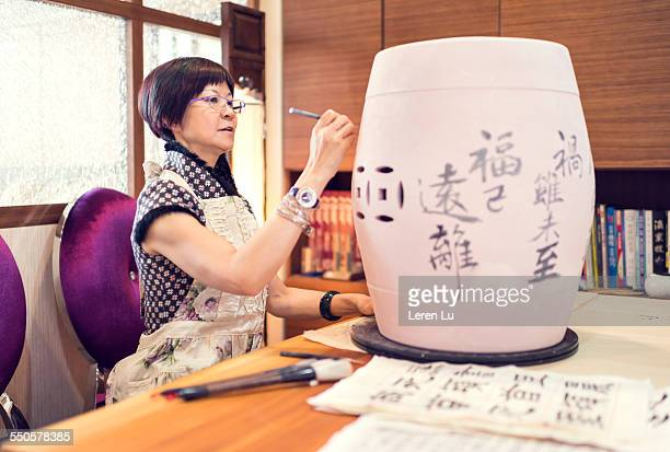 woman carving on blank of pottery jar - carving craft product stock pictures, royalty-free photos & images