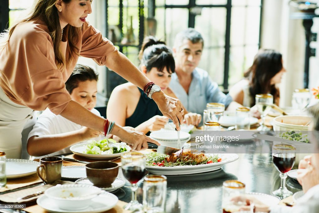 Woman carving roast chicken at dining room table during family celebration meal : Stock Photo