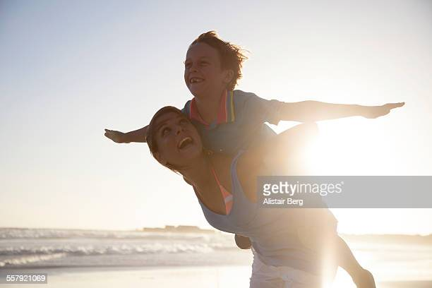Woman carying boy on beach