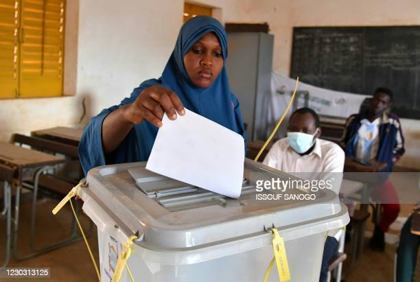 Woman cast her ballot at a polling station in Niamey on December 27, 2020 during Niger's presidential and legislatives elections. - Voters in the...