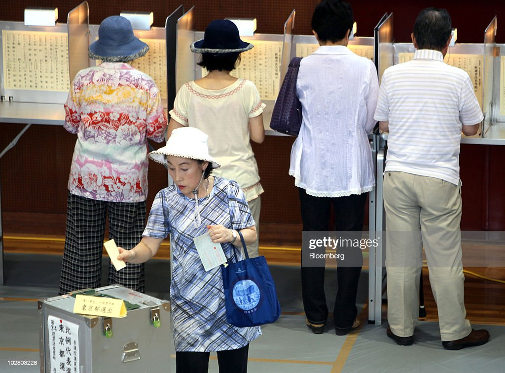 A woman casts a ballot at a polling station in Tokyo, Japan, on Sunday, July 11, 2010. Japanese voters fill in their ballots today with polls showing Prime Minister Naoto Kan's Democratic Party of Japan may lose control of the upper house of parliament, its biggest setback since taking power 10 months ago. Photographer: Toshiyuki Aizawa/Bloomberg via Getty Images