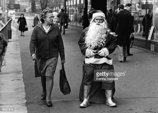 A woman casts a sceptical glance at a rather surly looking man dressed as Santa in a busy shopping street