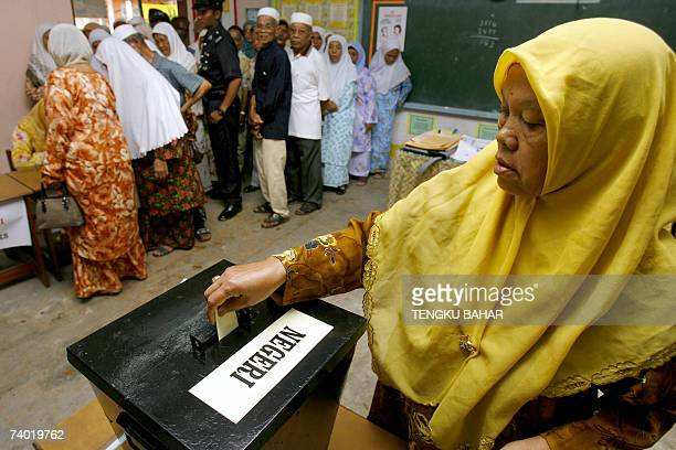 A woman casts her ballot as other voters crowd over a registration table at a polling station in Ijok in Selangor state 28 April 2007 Malaysia's...