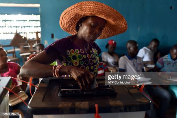 A woman casts her ballot as she votes at a polling station in Monrovia during presidential elections on October 10 2017 Liberians began voting on...