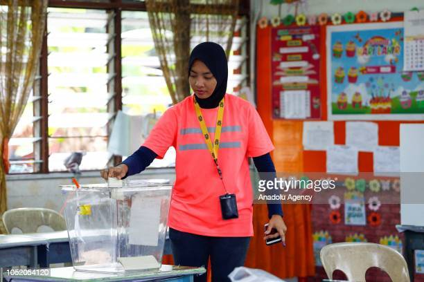 A woman casts her ballot at a polling station during the byelection in Port Dickson on October 13 2018 The Port Dickson seat was vacated to enable...