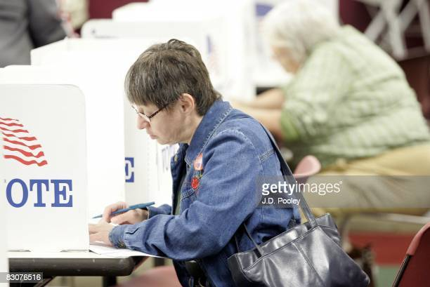 A woman casts her ballot during early voting October 1 2008 in Toledo Ohio No fault absentee voting allows any registered Ohioan to vote in the...