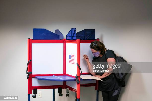Woman casts her ballot for the 2020 presidential election at an early voting location on October 1, 2020 in Alexandria, Virginia. Virginia's early...